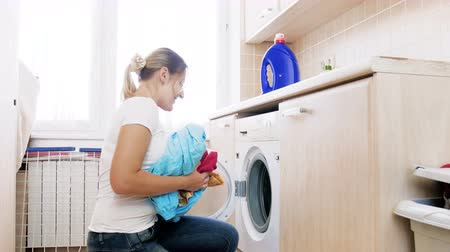 suszarka : 4k footage of young beautiful housewife loading washing machine with dirty clothes