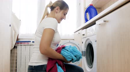 suds : 4k video of beautiful smiling woman putting dirty clothes in washing machine drum and swittching it on