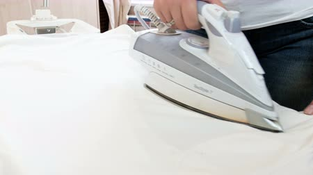 housekeeper : Closeup 4k footage of young housewife ironing white clothes on ironing board Stock Footage