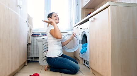 excesso de trabalho : Slow motion footage of happy cheerful housewife throwing clothes clean clothes at laundry