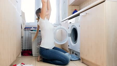 excesso de trabalho : Slow motion video of happy laughing woman taking clothes out of washing machine and throwing in air