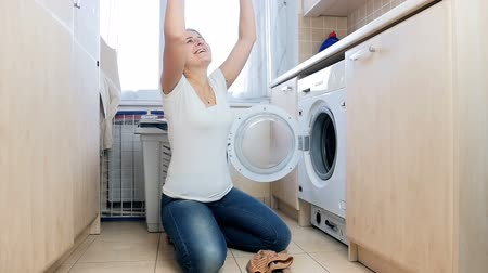 excesso de trabalho : Slow motion footage of laughing cheerful housewife having fun in laundry and throwing clothes