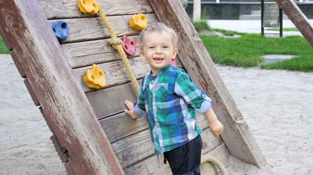 каратэ : Slow motion video of cheerful smiling toddler boy playing on playground with wooden wall for climbing