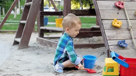 full bucket : Slow motion video of cute toddler boy digging sand and pouring in plastic bucket on playground at park