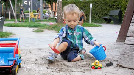 playful infant : Slow motion video of cute little boy playing in sandbox at park