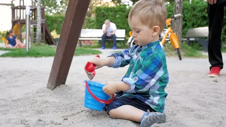 full bucket : Slow motion video of adorable 2 years old toddler boy digging sand and pouring it in bucket at park Stock Footage