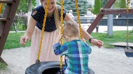 kreş : Slow motion of happy young mother swinging her toddler son on swing at park Stok Video