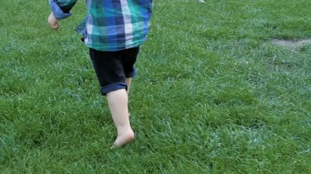esportivo : Slow motion closeup footage of adorable toddler boy feet running on fresh green grass at park
