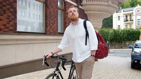 bricks : 4k video of stylish bearded man walking with retro fixed gear bicycle on street