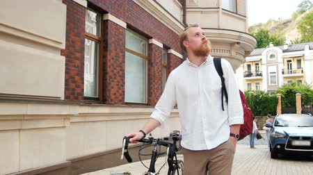 arriving : 4k footage of handsome hipster man with vintage bicycle walking on street of old town Stock Footage