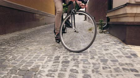 estreito : 4k footage of stylish man riding black vintage bicycle om paved road of narrow street