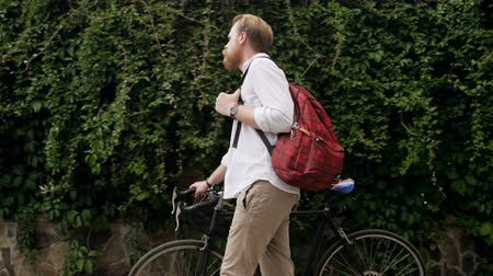 bruk : 4k video of stylish young bearded man with bag walking with bicycle on street Wideo