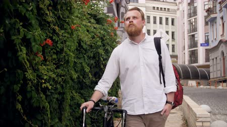 nem városi színhely : 4k footage of stylish red bearded man with bicycle walking on street