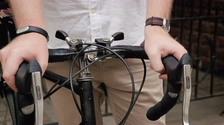 arriving : Closeup 4k footage of male hands on vintage sports bicycle handles