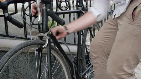 thieve : Closeup 4k footage of young man locking bicycle to fence with chain lock