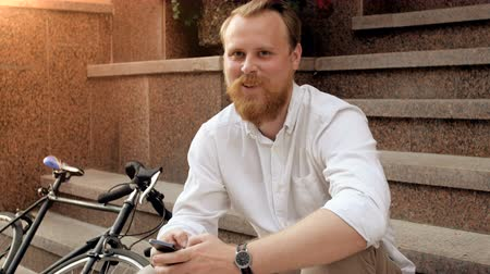 bikers : 4k portrait of happy smiling red bearded hipster man sitting on staircase
