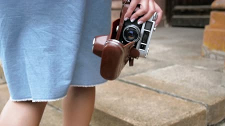 spying : Slow motion closeup video of young woman walking with vintage film camera