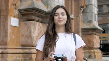 film camera : Slow motion footage of young smiling woman making photographs while walking on street