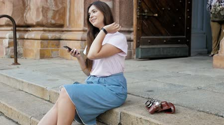 послать : Slow motion footage of beautiful tourist girl sitting on street and using smartphone
