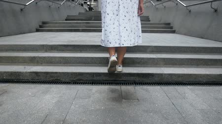 spor ayakkabısı : Slow motion footage of young girl in white dress and sneakers walking up the stairs Stok Video