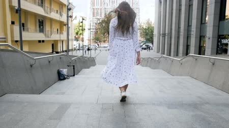 skákání : Slow motion footage of cheerful girl with long hair walking down the stone stairs on street Dostupné videozáznamy