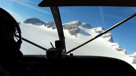летчик : Video from the private airplane cockpit of flying at snowy moutains Стоковые видеозаписи