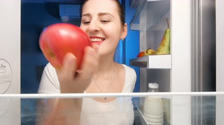 поздний завтрак : 4k footage of beautiful young woman taking and eating red apple from refrigerator Стоковые видеозаписи