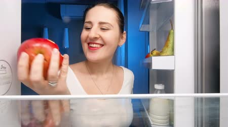 поздний завтрак : 4k footage of young smiling woman opens refrigerator and bites red juicy apple