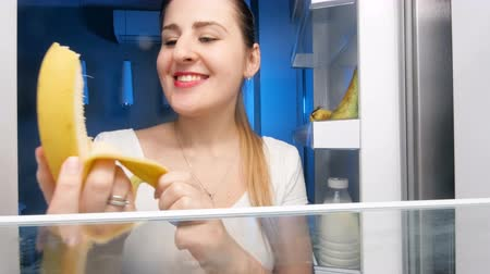 supermarket food : 4k footage of young smiling woman taking banana from refrigerator, peeling and biting it