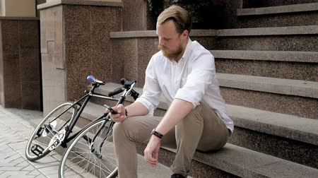 ciclismo : Slow motion video of stylish hipster man sitting on staircase and typing message on smart phone