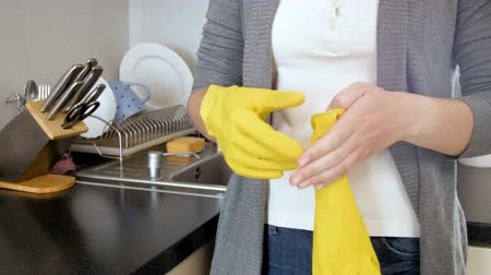 tecido : 4k footage of young housewife wearing yellow latex gloves while doing housework