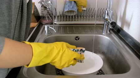 gorduroso : 4k closeup footage of young housewife in protective latex gloves washing dishes in kitchen sink
