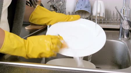 higiênico : Closeup 4k footage of housewife washing off detergent suds from dishes in kitchen sink