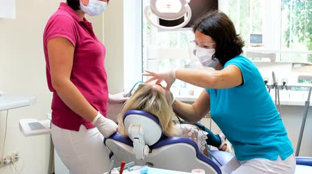 escova de dentes : 4k footage of female dentist working with patient lying in dental chair
