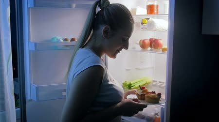 bir genç kadın sadece : Slow motion video of young woman looking for something to eat at night. She chooses healthy begetables instead of cake