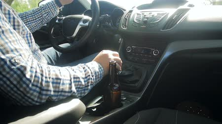 itself : Young man driving car with bottle of beer. Driving after drinking alcohol is dangerous.