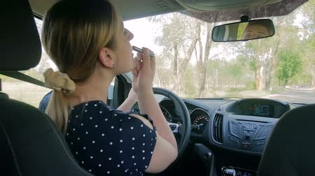 irresponsible : Slow motion footage of young female driver applying lipstick while driving car