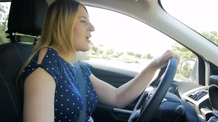 sluch : Slow motion footage of happy young woman driving car and singing Dostupné videozáznamy