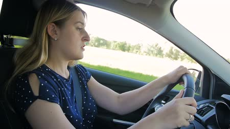 ülés : Slow motion footage of young woman feeling very tired and falls asleep while driving car