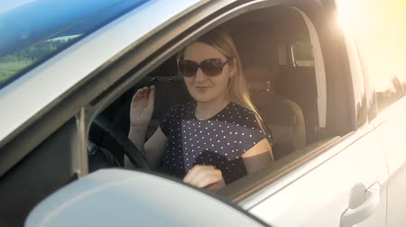 yönlendirmek : Slow motion footage of young female driver wearing sunglasses driving car Stok Video