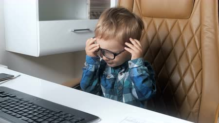 předstírat : 4k video of cute smiling little boy sitting in office chair and playing with eyeglasses Dostupné videozáznamy