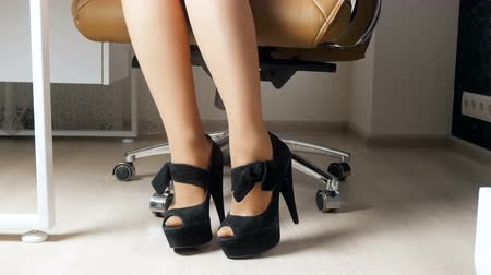 stockings : 4k footage of elegant businesswoman wearing long heels sitting in office chair