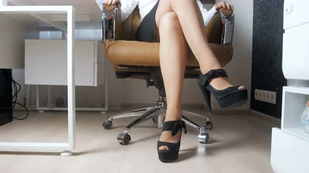 calçados : 4k video of elegant busineswoman with long sexy legs in high heels sitting on big boss chair at office