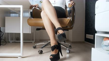 iğfal : 4k video of sexy young owman with long legs posing in big boss office chair Stok Video