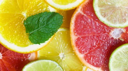 grejpfrut : Closeup 4k footage of camera moving along slices of lemons, oranges, limes and grapefruits with mint leaves