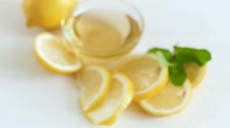 grejpfrut : Camera zooms and focuses on lemons with honey lying on white wooden table