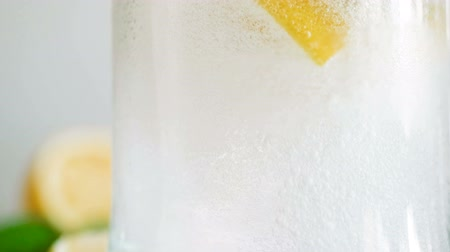 ice cube : Closeup slow motion video of pouring cold water in glass with lemonade