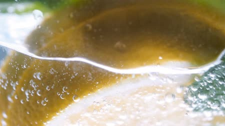 citron : Macro footage of pouring carbonated water in glass of lemonade Stock Footage