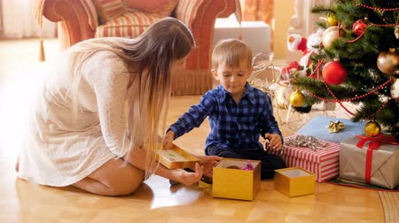 presentes : 4k video of adorable toddler boy sitting on floor with mother under Christmas tree and opening gift box with presents
