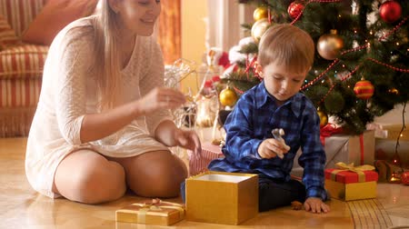 bonitinho : 4k footage of happy laughing little boy sitting under Christmas tree and taking toys out of gift box